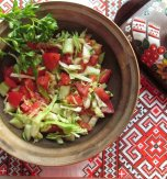 Cabbage, cucumber, and tomato salad dressed with olive oil